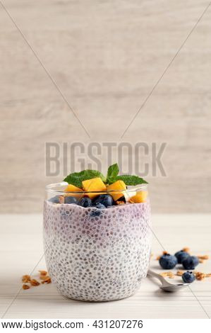 Delicious Chia Pudding With Blueberries, Mango And Mint On White Wooden Table, Space For Text