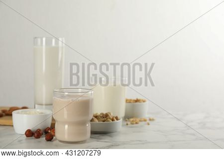 Different Vegan Milks And Ingredients On White Marble Table. Space For Text