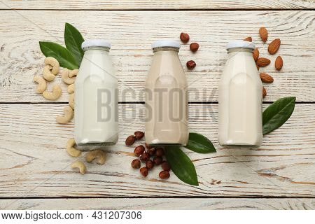Different Vegan Milks And Nuts On White Wooden Table, Flat Lay