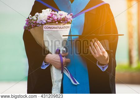 Education Theme Concept. Graduate Holding A Hat And Flowers.