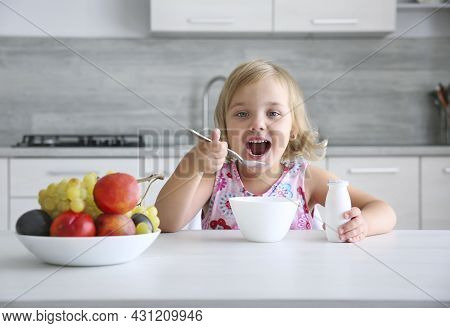 Child Girl Eating Healthy Food.smiling Little Girl Have A Meal At Kitchen.kid Have Fruits And Yogurt