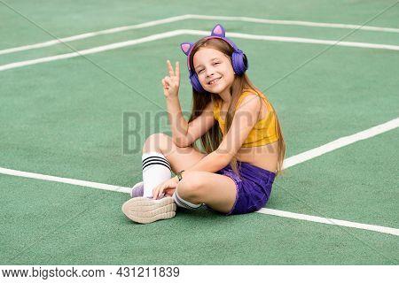 Fashion Pretty Cool Smiling Preteen Kid Schoolgirl In Wireless Headphones Listening To Music Wearing
