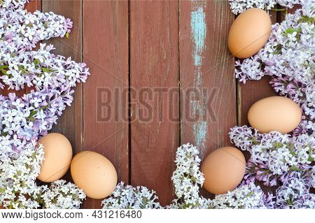 Brown Eggs Of Domestic Hens And Lilac Flower On Old Red Wood Texture Background. Spring And Easter C
