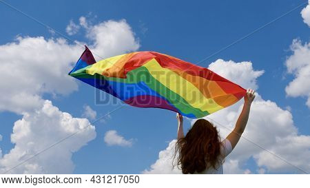 Bisexual, Lesbian, Woman, Transgender Holds Lgbt Flag In The Background Of Blue Sky With Clouds On A