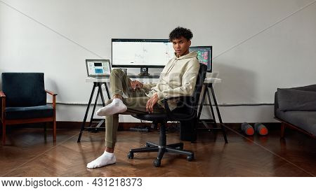 Full Length Shot Of Young Mixed Race Man Trading Online Using Laptop And Computer, Sitting At Home I