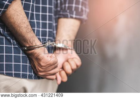 Prisoner Man In Jail With Handcuffs. Close Up Shackled In Hands.