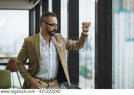 Young Handsome Business Bearded Man Standing Post Near Window In Office Work Place.