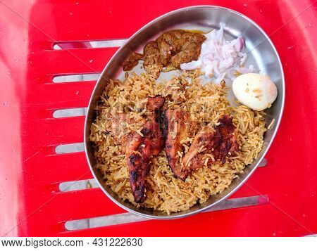 Top View Of Eating Plate Filled With Chicken Biryani, Two Tandoori Chicken, One Boiled Egg , Raitha