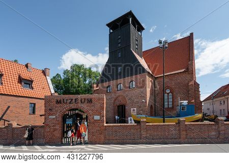 Hel, Poland - 08.01.2021: People Entering Red Brick Building Of The Museum Of Fishing In Hel, A Depa