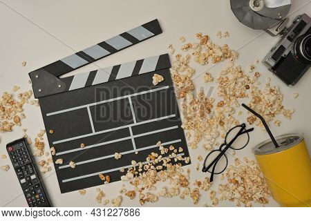 Above View With Popcorn Spilled On The Table And Clapper Board, Remote, Eyeglasses, Vintage Camera A