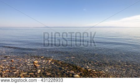 Clear Fresh Water And  Panorama Of Lake Baikal On A Summer Day. Landscape With The Blue Surface Of T