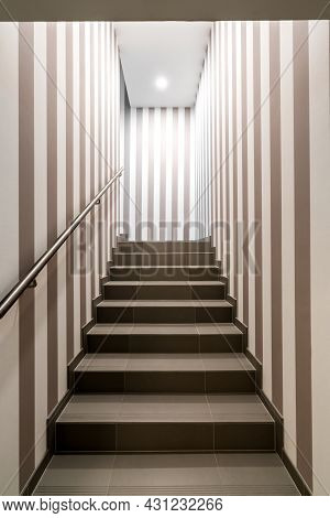 Vertical Shot Of Gloomy Lit Staircase With Vertical Dark And White Stripes On The Walls. Concept For