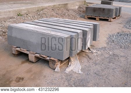 The Pallet With A Stack Of Concrete Curbstone. Stack Of Gray Curbstone On Pallet Standing On Pavemen