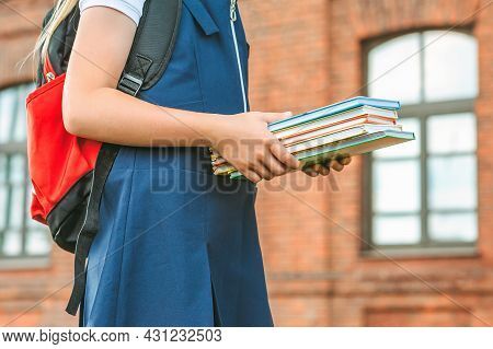 Close-up, A Child Of An Elementary School Student Holds Books In Her Hands And Goes Back To School.