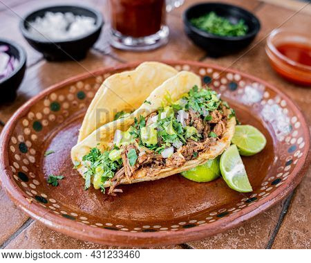 Delicious Mexican Style Birria Taco, Accompanied With Onion, Cilantro And Lime, Served In A Clay Dis