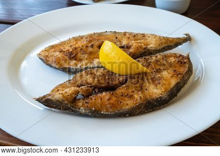 Closeup Shot Of Freshly Fried Halibut Fillets With Lemon On A White Plate In A Local Pub In Jastarni