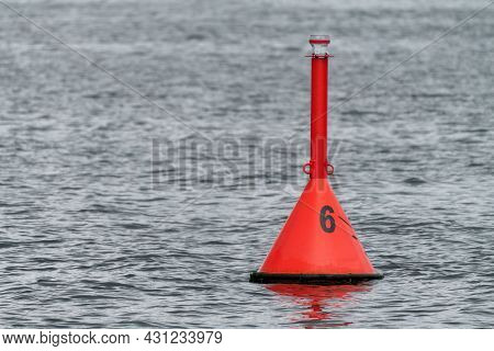 Red Water Buoy With Number 6 On It Floating In The Baltic Sea Near Hel, Poland, On A Cloudy Day.