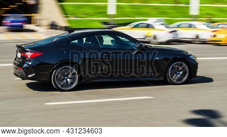 Black Bmw 420i G22 Coupe On The Road In Motion. Fast Speed Drive On City Road. Side View Of Moving B