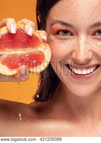 Natural Smiling Girl With Fresh Grapefruit. Beauty Model Squeezing Juicy Fruit.