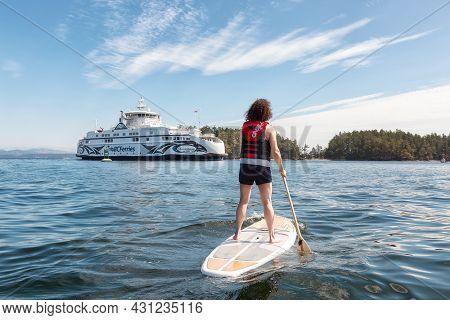 Victoria, Vancouver Island, British Columbia, Canada - August 15, 2021: Adventurous Woman Paddle Boa