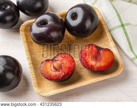 Black Plums Whole And Cut In Half On A Square Wooden Plate Over Table. Ready To Eat Fresh Ripe Plums