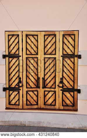 Wooden Shutters On The Windows. A Large Window In The House Is Closed By Shutters With Large Metal H