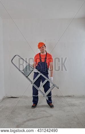A Builder In An Orange Helmet Makes Repairs