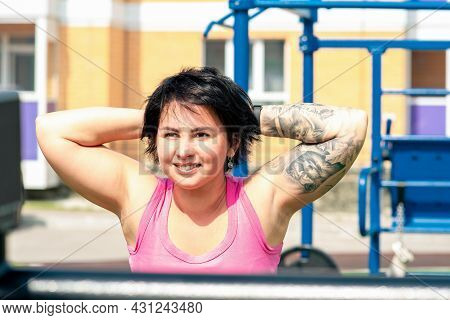 Young Woman Performing Back Extension Exercises In The City Yard Using Street Exercise Machine Hyper