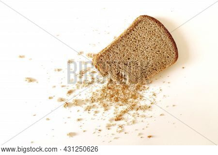 A Slice Of Rye Bread On A White Surface, Bread Crumbs Scattered Nearby