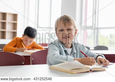 Happy Schoolkid Smiling At Camera Near Asian Boy Writing On Blurred Background