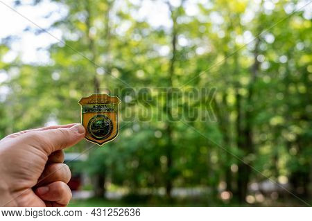 Acadia, Maine, Usa. 8-2021: Acadia National Park Junior Ranger Pin Held Against A Green Forest Backd