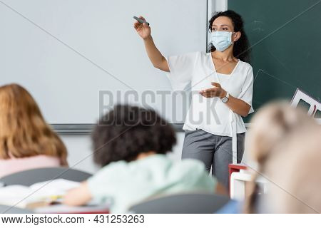African American Woman Pointing With Hand Near Whiteboard And Blurred Schoolkids