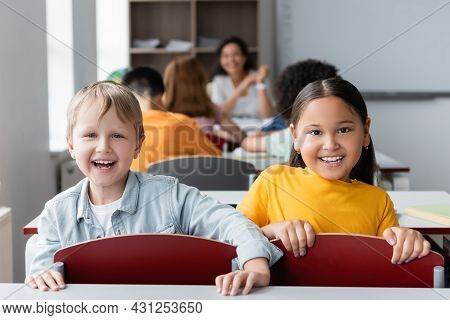 Cheerful Interracial Schoolkids Looking At Camera Near Blurred Classmates And African American Teach