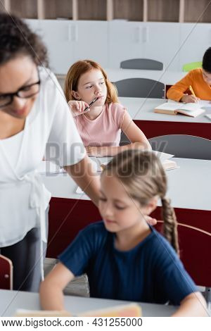 Selective Focus Of Thoughtful Redhead Girl Near Blurred Multiethnic Classmates And African American