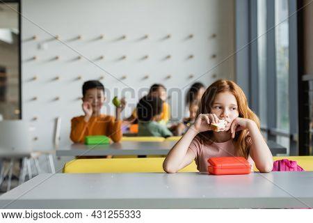 Sad Redhead Girl Eating Sandwich Near Schoolkids On Blurred Background