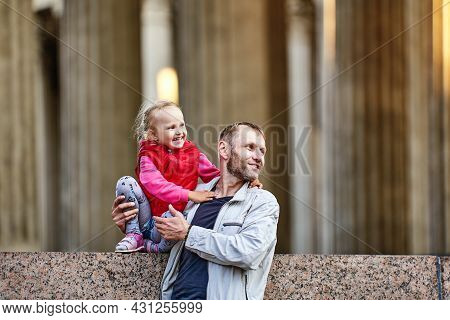 Father And Smiling Baby Walks Near Columns.