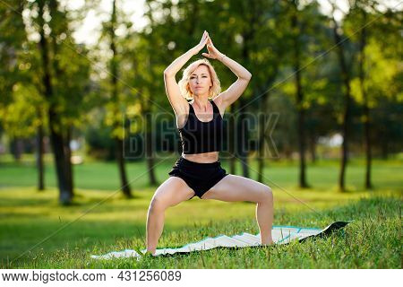 Yoga Training By Woman On Mat In Garden.