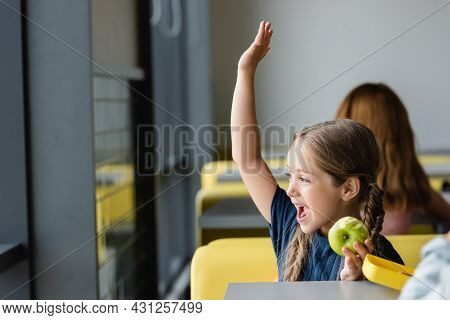 Astonished Girl With Fresh Apple Waving Hand While Looking Away In School Canteen