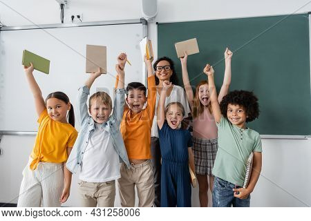 Excited Multiethnic Schoolkids Holding Books In Raised Hands Near Happy African American Teacher