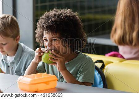African American Schoolboy Eating Apple Near Blurred Classmates In School Canteen