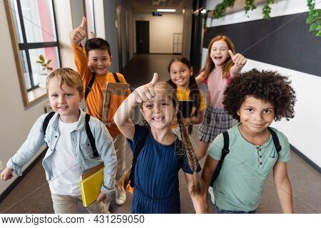 Cheerful Multicultural Schoolchildren Showing Thumbs Up In School Corridor