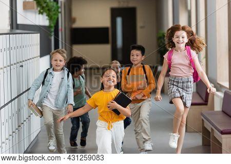 Excited Redhead Girl Jumping Near Multiethnic Classmates Running In School Corridor