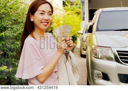 Asian Businesswoman Holding Banknotes, Cash And Car Keys, Is Well Equipped To Finance And Manage Aut