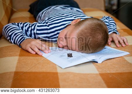 Boy Fell Asleep While Lying On The Couch Reading A Book Or Doing Homework. The Son Got Tired Of His