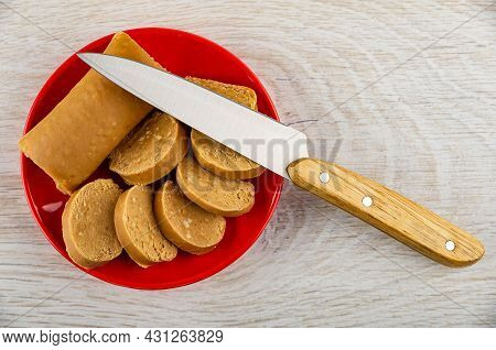 Kitchen Knife On Red Saucer With Sweet Creamy Sausage With Peanut (oriental Sweets), Slices Of Sweet