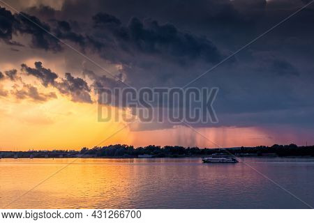 A Small Ship Is Sailing Along The River Against The Backdrop Of The Sunset. Rain Clouds In The Sky.