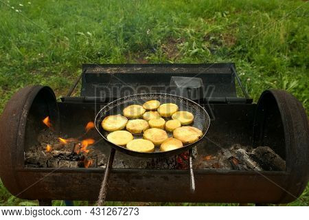 Slices Of Zucchini Is Frying On Frying Pan With Oil On Coals In The Grill On Nature. Preparing Food