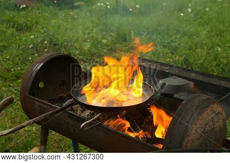 Man Is Frying Slices Of Fresh Organic Zucchini On Frying Pan With Hot Boiling Oil On Coals In Grill.