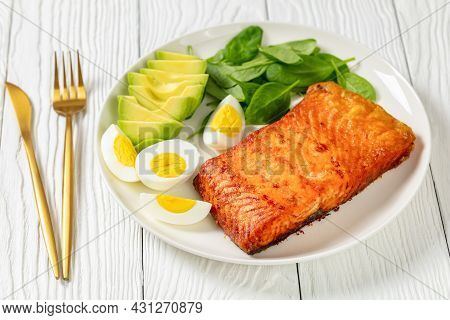 Oven Baked Salmon Fillet With Creamy Ripe Avocado, Baby Spinach And Hard Boiled Eggs On A White Plat