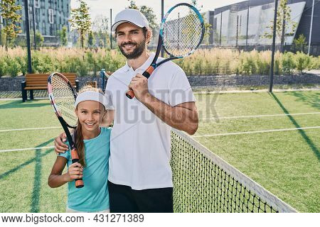 Portrait Of Father Tennis Player And Little Daughter In Sportswear With Rackets In Hands On Tennis C